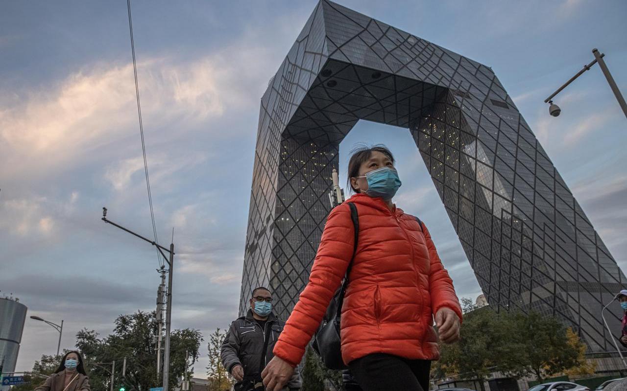 Een vrouw in Beijing draagt een mondkapje in het zakencentrum van de stad.