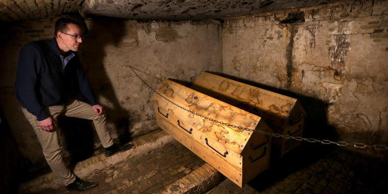 André Buwalda in de gerestaureerde grafkelder. De stoffelijke resten van Schelte van Aysma worden in een kist geplaatst; de overblijfselen van zijn familieleden komen in de andere.
