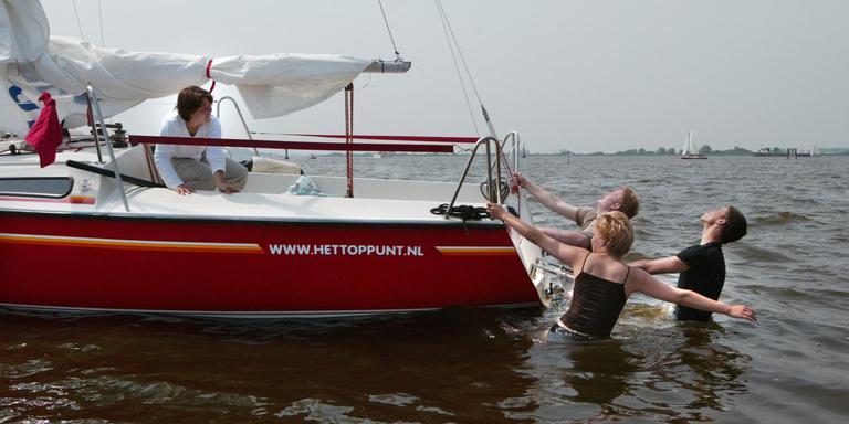 Een kajuitzeiljacht is vastgelopen op de Koevorde. De bemanning moet overboord om het schip vlot te trekken. FOTO LC