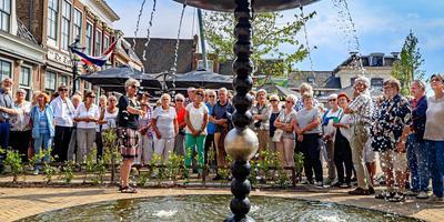 Artistiek leider Anna Tilroe (links, met microfoon) van de 11 Friese fonteinen geeft uitleg over de fontein van Jean-Michel Othoniel in Franeker, die is geïnspireerd op astronoom Jan Hendrik Oort, die in de stad werd geboren. FOTO NIELS DE VRIES