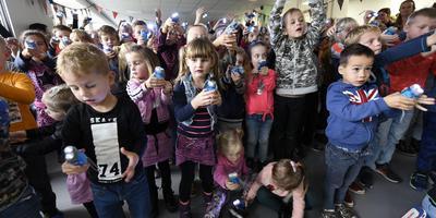 Door massaal te schijnen met een knijpkat openden leerlingen van De Leister Ikker in Opeinde gisteren hun totaal vernieuwde school. Foto Marchje Andringa