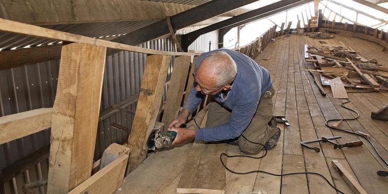 Een vrijwilliger werkt aan het bovendek van het schip. FOTO JAN DE JAGER