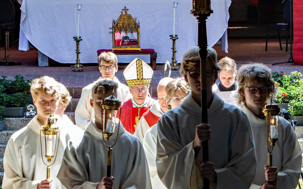 Bisschop Ron van den Hout verlaat geflankeerd door acolieten de Bonifatiuskapel.