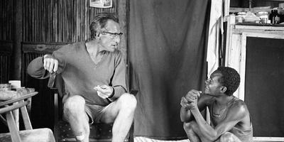 Sibbele Hylkema praat in 1967 met een huisjongen. Ondertussen draait hij shagjes voor zichzelf en zijn bezoekers.