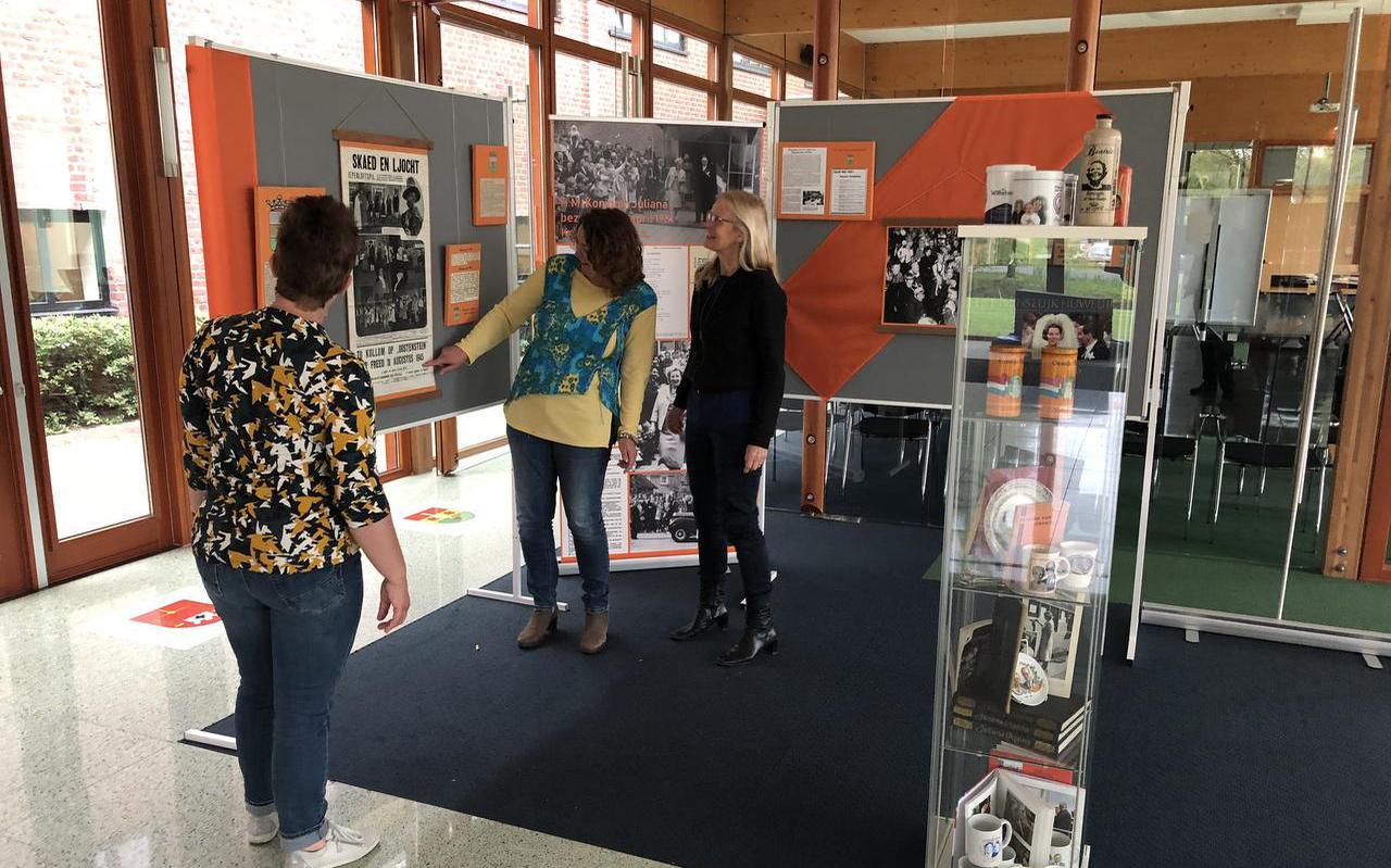 Minke van der Veen (l), Maaike Terpstra (m), Jettie Teenenga (r) onthullen vandaag de expositie honderd jaar Oranjecomite Kollum. FOTO LC