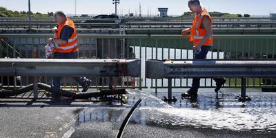 Medewerkers van Arcadis houden het brugdek van de noordelijke draaibrug in de Lorentzsluizen nat om uitzetting te voorkomen. Rijkswaterstaat legt nu een automatisch koelsysteem aan. FOTO NIELS DE VRIES