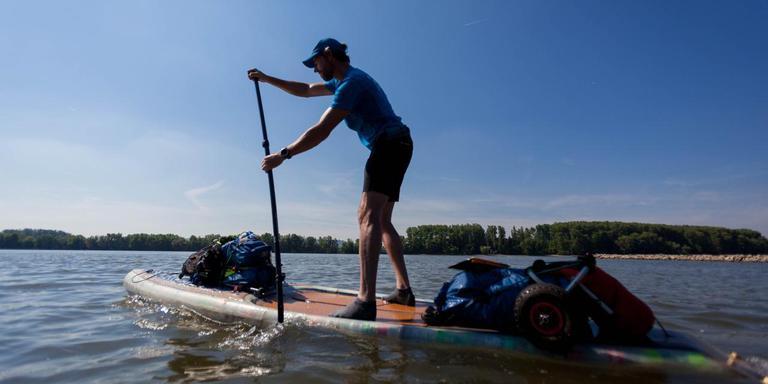 Performancekunstenaar Merijn Tinga, alias de PlasticSoupSurfer, tijdens zijn sup-tocht over de Rijn. FOTO EELKE DEKKER