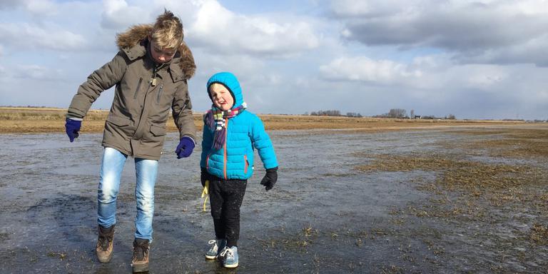 Jesmar (9) en Jente (4) Oosterveld en hun moeder Bothilda de Boer uit Akkrum inspecteren het ijs op de Blau Gerzen.