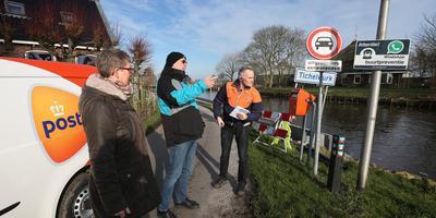 Bewoners van Tichelwurk, met links Liesbeth Poortman, praten met de postbode over het verdwijnen van de brievenbus. Straks moeten ze over de Dokkumer Ie naar Wyns.