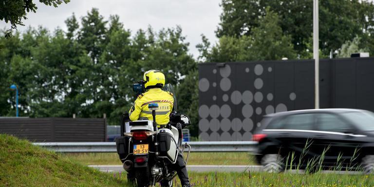 Een motoragent controleert het verkeer op de N31 bij de op- en afrit naar Opeinde en Nijega. FOTO JILMER POSTMA