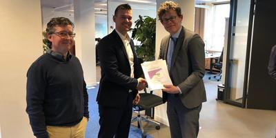 Kevin van Doeveren en Sake van der Veen (midden) overhandigen hun zienswijze op het ministerie aan directeur Meindert Smallenbroek.