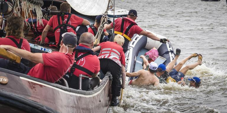 Het skûtsje van Drachten schampt het grijze rubberbootje. De opvarenden raken te water. Op de voorgrond met pet schipper Jeroen Pietersma. FOTO TOM COEHOORN