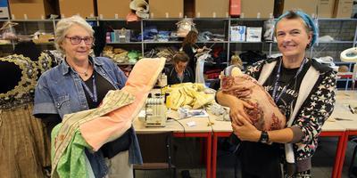 Nanna Franconi (links) en Elvira van Bentum met geleende waar van kostuumhuis Angel en een stoffen baby. In de dozen op de achtergrond werd alle kleding opgestuurd. FOTO NIELS WESTRA