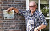Rinze Post laat foto's zien van de scheuren die in de (door hemzelf gerestaureerde) muren van zijn huis in Wijnaldum zaten. FOTO HENK JAN DIJKS