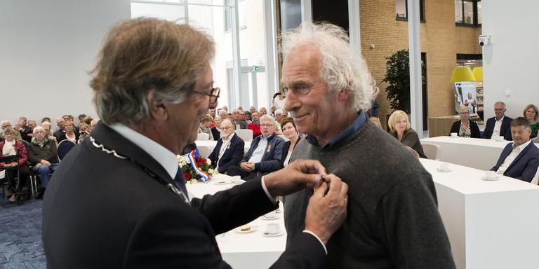Waarnemend burgemeester Hayo Apotheker van Waadhoeke speldt Jan Posseth uit Marsum zijn koninklijke onderscheiding op. FOTO HOGE NOORDEN/JAAP SCHAAF.