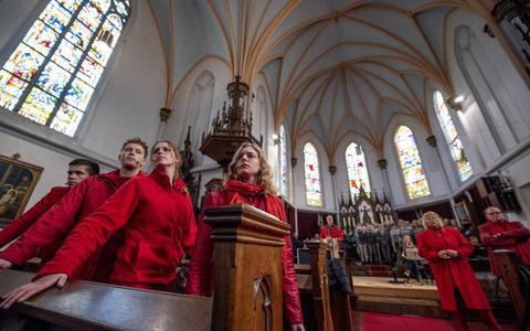 Oefenen voor  Tusken twa tuorren  in de Martinuskerk van Wergea. De rode kleding is ontleend aan de rode mantel van Sint-Maarten.