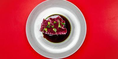 Geroosterde knolselderijsteak met palmboomsalade, een cracker van rode biet en groentejus. FOTO'S NIELS DE VRIES