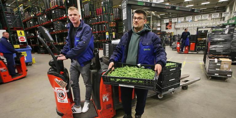 De Poolse orderpickers Dawid Wachowski (l) en Maciej Zak aan het werk bij Smeding Groenten en Fruit in Sint Annaparochie FOTO NIELS WESTRA