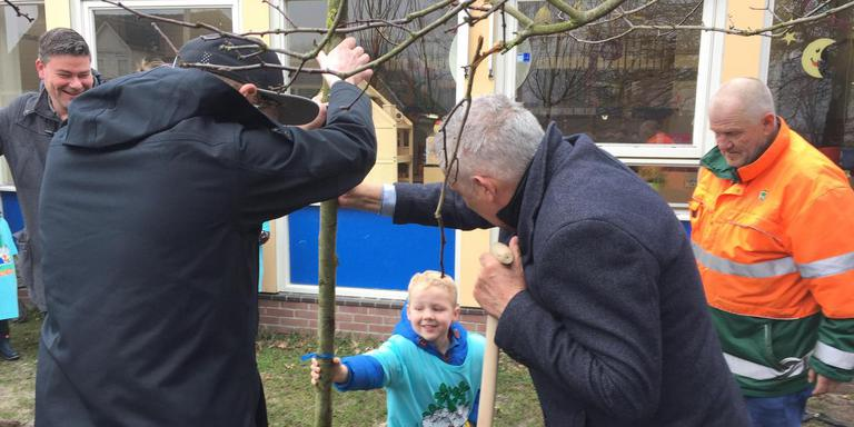 De vierjarige Thieme Hielkema plant een van de bomen van de levende tipi op het school van OBS De Hoekstien. Hij krijgt hulp van wethouder Wietze Kooistra en presentator Raynaud Ritsma.