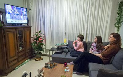 Marijke Krijgsman kijkt met haar dochters Melissa (roze trui) en Mara naar de inauguratie op tv.