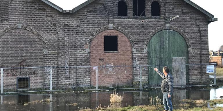Jan-Willem Tuininga (FNP) staat op het voormalige rangeerterrein met loods in Stiens waar 58 levensloopbestendige woningen zouden moeten komen. Foto LC