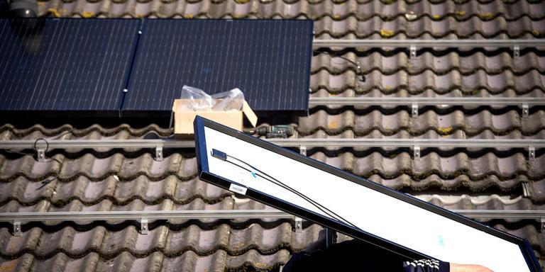 Een installateur plaatst een zonnepaneel op een dak in Drachten. Door de hitte behalen de panelen momenteel niet hun maximale rendement. FOTO JILMER POSTMA