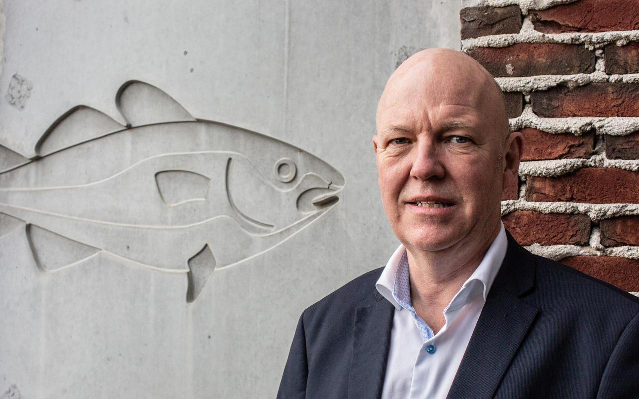 Joop de Jong, scheidend directeur van de Amelander Musea bij een reliëf van Gunnar Daan, die het Natuurmuseum in Nes ontwierp.
