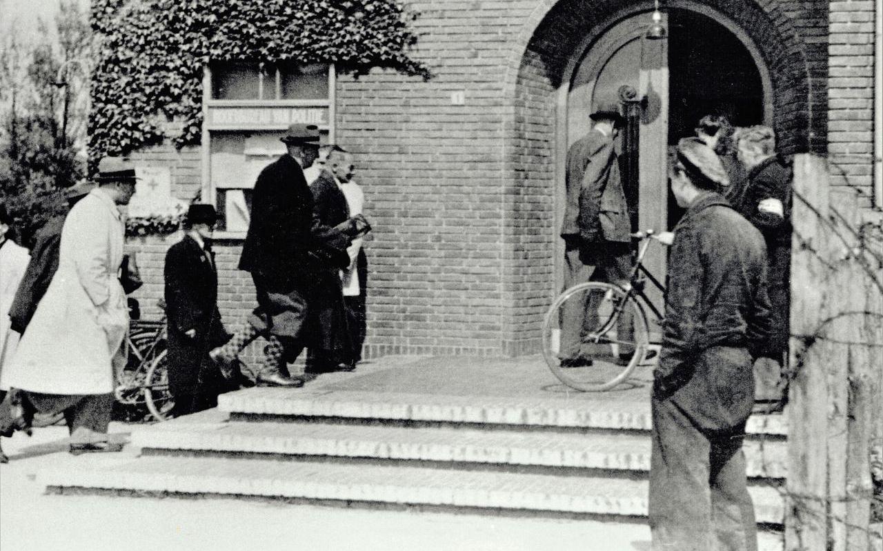 De aankomst van gearresteerde Tjeerd van der Weide (met geblokte sokken onder zijn knickerbocker) bij het Hoofdbureau van Politie in IJmuiden.