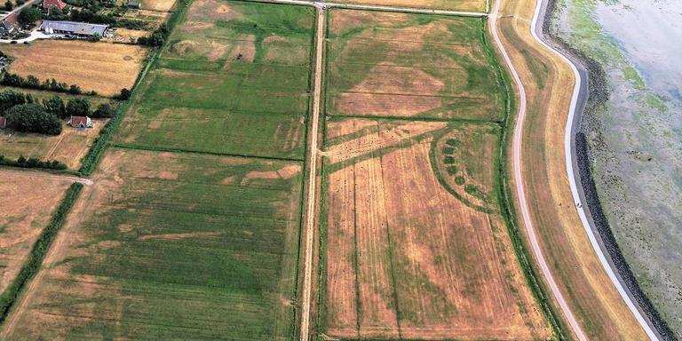 De foto toont een halvewielvorm bij de Waddendijk op Terschelling ter hoogte van Oosterend. Hier lag vroeger een vijver (wiel) als overblijfsel van een dijkdoorbraak. Links hiervan lopen lijntjes. Het zijn de overblijfselen van een historische dijk en dijksloten die hoeks op de Waddendijk uitkwamen. FOTO TERSCHELLING.TV.