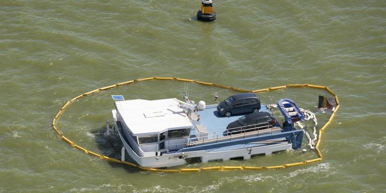De gele schermen moeten de uit het schip gelekte gasolie tegenhouden. FOTO ANP