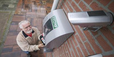 Maarten Jeronimus, voorzitter Dorpsbelang Fochteloo, bij de AED die wordt bewaakt door een camera.