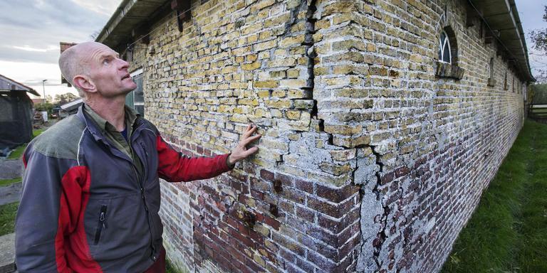 Pieter Dekker laat de scheuren zien in de muren van zijn woonboerderij aan de Lindedijk in Spanga. De inklinkende veenpolder verzwelgt het zuidelijkste gebouw van Friesland. FOTO RENS HOOYENGA