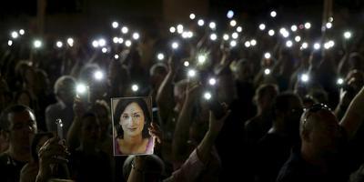 Demonstranten houden een portret omhoog van de vermoorde journalist Daphne Caruana Galizia, bij een met mobieltjes verlichte betoging in de hoofdstad Valletta op 16 september, elf maanden na de autobomaanslag. FOTO REUTERS/DARRIN ZAMMIT LUPI