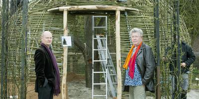 Het Australische kunstenaarsduo Jon Drummond (l) en Nigel Helyer in De Kruidhof in Buitenpost. Op de achtergrond de muziekinstallatie in wording, gemaakt van leem en wilgentakken in de vorm van een bijenkorf. FOTO MARCEL VAN KAMMEN
