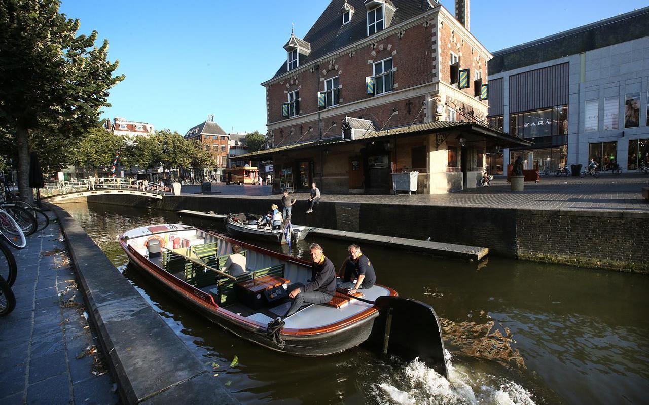 Schippers Zweitse Pietersen (l.) en Willem Barendrecht van Stichting Praamvaren passeren de Waag in Leeuwarden. Vanwege coronaregels zijn er nog maar een paar bankjes over in de boot.  FOTO NIELS WESTRA