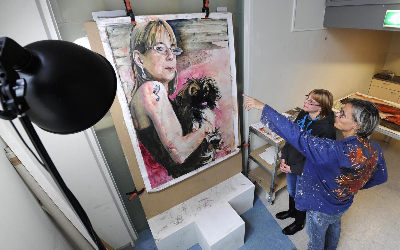 Yvonne IJtsma bekijkt het meer dan levensgrote portret, dat schilderes Mirjam Torenbeek (rechts) van haar en haar hondje Billy heeft gemaakt. FOTO PERSBUREAU NOORDOOST/ALEX J. DE HAAN