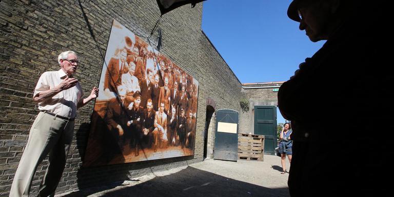 Gerrit Fokkema naast het portret van 'zijn' bevrijders. Rechts, in silhouet, Hans Sijses, weduwnaar van Rigtje Hofstra, een van de koeriersters die betrokken waren bij de Overval. FOTO NIELS WESTRA