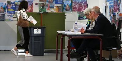 Leden van het stembureau Joke de Boer, Irma Belksma en André Busse (van links naar rechts) zitten op hun post terwijl er een stemformulier de bus in gaat. FOTO NIELS WESTRA
