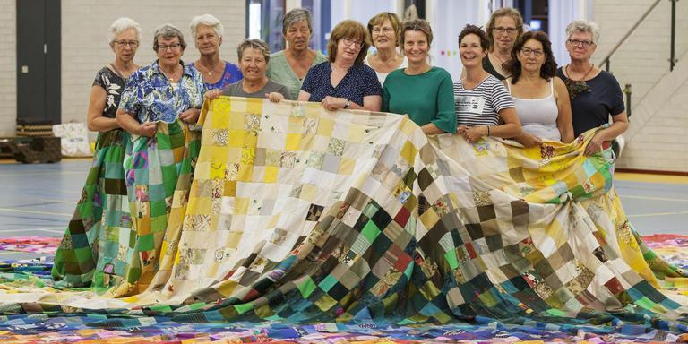De maaksters in de patchwork rok van 12 bij 12 meter, belangrijk in locatievoorstelling De verdwenen peerden. Vooraan derde en vierde van rechts artistiek leider Mariken Biegman en Sietske Bloemhoff. FOTO RENS HOOYENGA