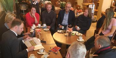 Met een notitieboek vol huiswerk keert Van der Molen huiswaarts. Op de rug gezien de docenten van de Friese Poort, aan de overkant van de tafel de melkveehouders Gea Asma en Willem van den Tweel. FOTO LC
