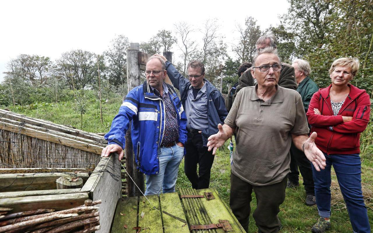 Kooiker Piet Inia (op de voorgrond) leidt de genodigden rond in de kooi waar hij normaal geen gasten ontvangt. FOTO HENK JAN DIJKS