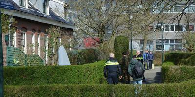 Politiemensen en experts van de EOD bij de tuin waar bewoners zondagochtend een handgranaat aantroffen. FOTO VAN OOST MEDIA