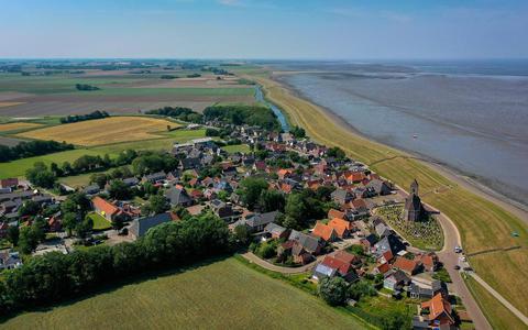 Zicht op Wierum aan de Waddenzeedijk. Ooit was de Mariakerk het middelpunt van het dorp. Maar door een storm verdween het noordoostelijke deel van de terp waar de kerk op stond, en daarmee een deel van het dorp.