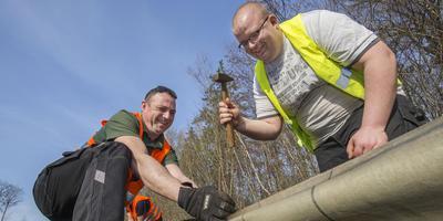 Michiel Brandenburg (rechts) en Frans de Vries plaatsen paddenschermen in het Kuinderbos. FOTO RENS HOOYENGA