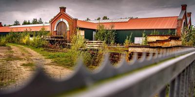 Het onkruid staat hoog op het terrein rondom de nooit gebruikte en nieuw gebouwde remise in Sneek.