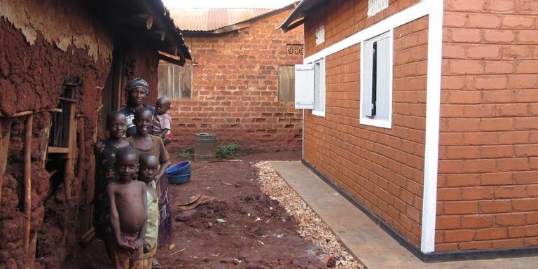 Een grootmoeder en haal kleinkinderen in Jinja in Oeganda. Links hun oude huisje, rechts het nieuwe huis dat gebouwd is met hulp van Grannies2grannies.