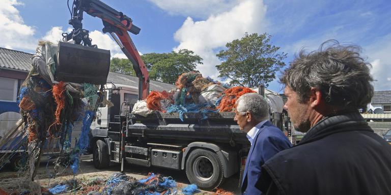 Burgemeester Bert Wassink (links) ziet toe hoe Douwe Sieperda de ingezamelde visnetten oplaadt. FOTO JAN HEUFF