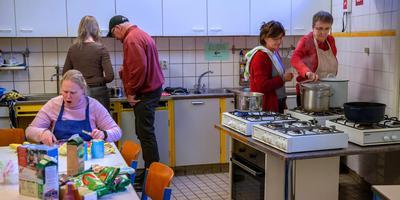 De stamppot wordt voorbereid in de keuken van De Skûle. Rechts deelneemster Marian met begeleidster Hinke Dijkstra, links deelneemster Marijke en op de rug gezien vrijwilliger Marrit van der Hoest met een cliënt. FOTO NIELS DE VRIES