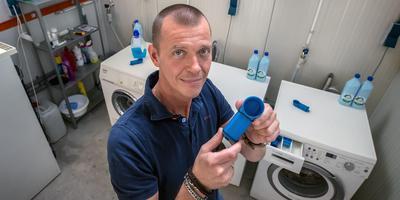 Theo Brens showt het bakje waarmee vloeibaar wasmiddel gedoseerd in de machine kan worden gebracht. FOTO NIELS DE VRIES