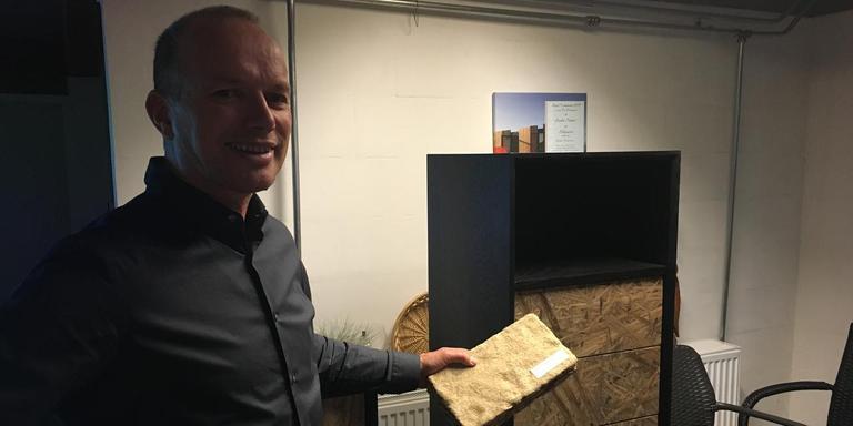 Eddy Wymenga bij een kast met lisdoddelaminaat. Hij heeft een stuk isolatiemateriaal van lisdodden in zijn hand.